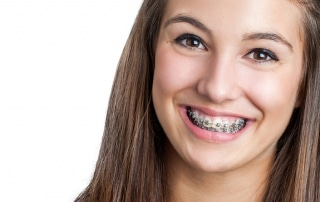 Smiling Teen girl showing dental braces.