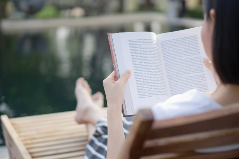 woman reading a book while relaxing outdoors
