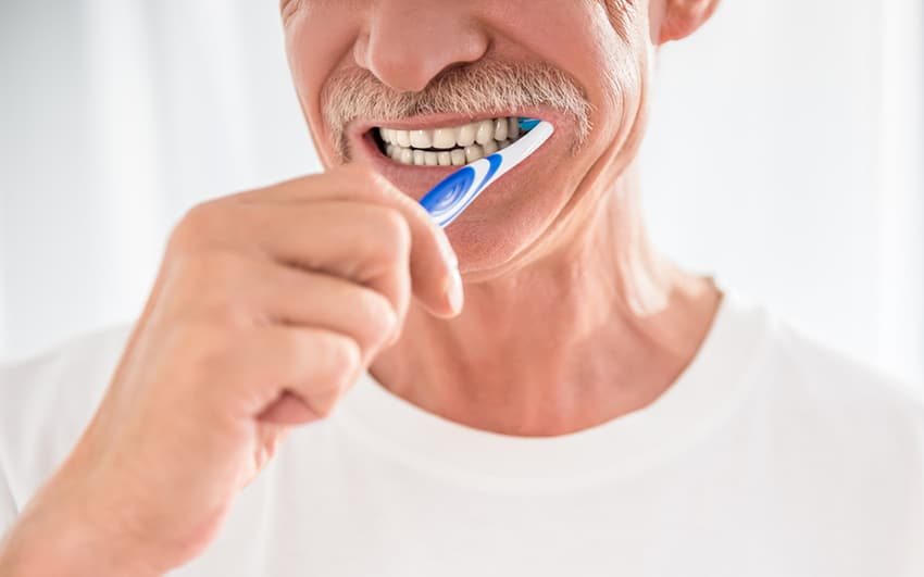 Senior man is cleaning his teeth and smiling.