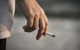 Man's Hand Holding a Cigarette