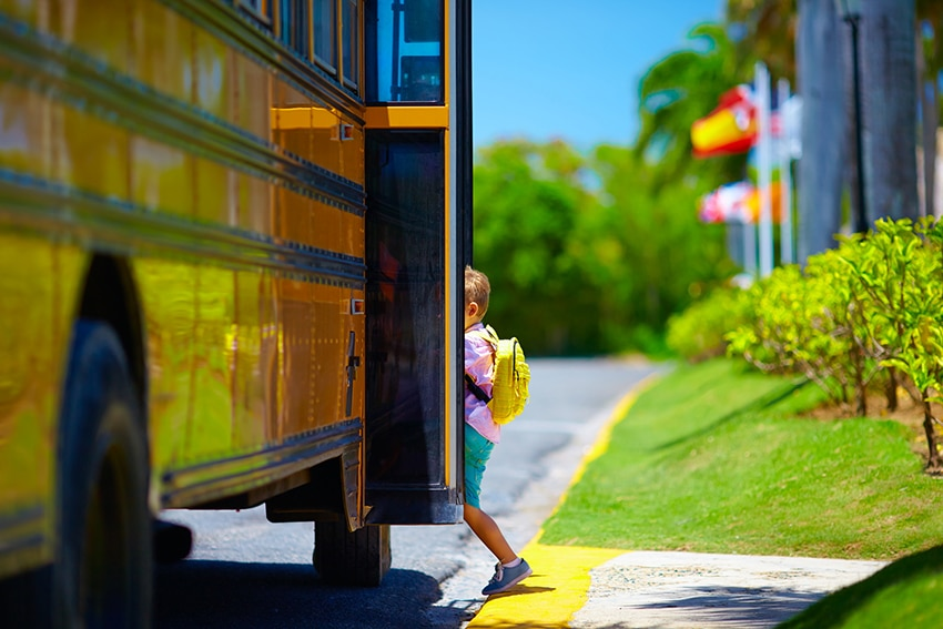 A kid getting on a school bus