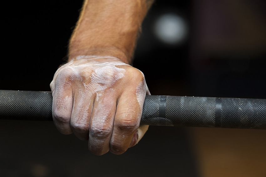 A hand with chalk on it preparing to lift a heavy weight