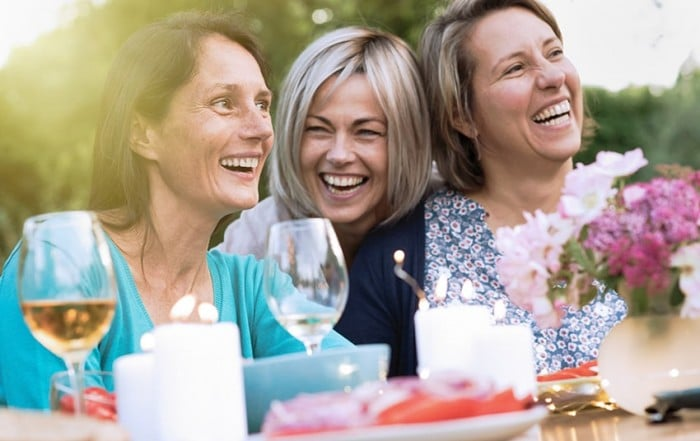 Group of middle aged woman enjoying eachothers company at a party. Each makes sure they schedule regular checkups to prevent gum disease.