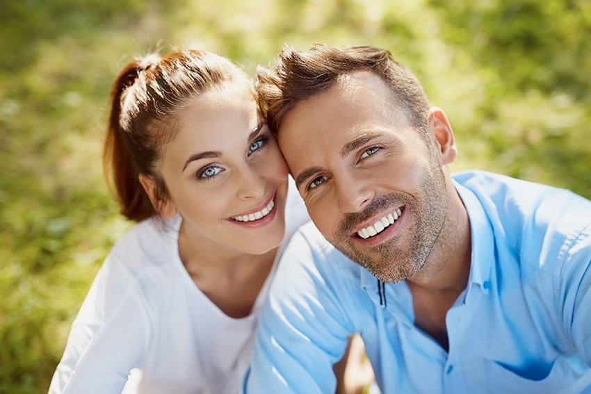Closeup of a young happy couple looking at a camera - proud of their perfect smile