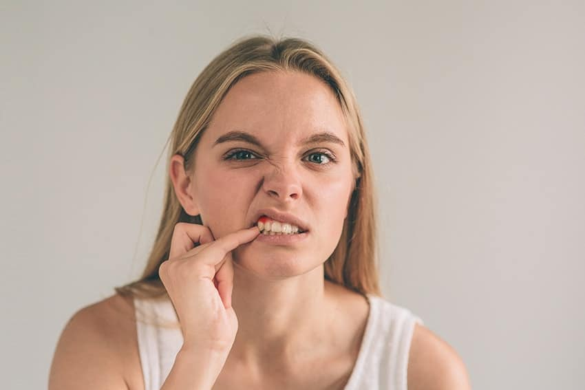 Young blonde haired woman inspects her gumline with her pinky finger, wondering what's lurking in her Gums. Did you know that at any given time, there are around 8 billion bacteria living inside your mouth?