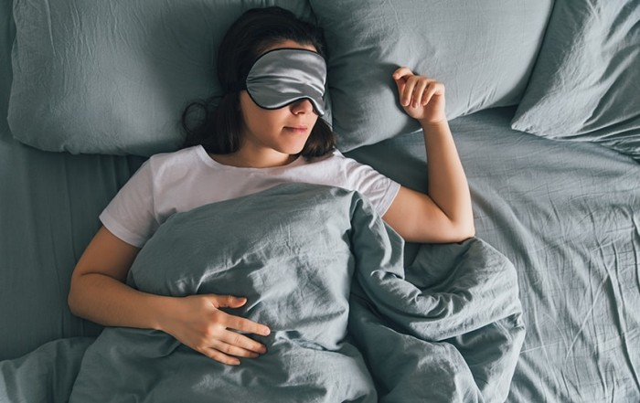 Young woman rests peacefully on grey sheets while she wears an eye patch to keep the light out of her eyes. She's learning to prioritize her sleep which helps boost her immune system and prevents depression.