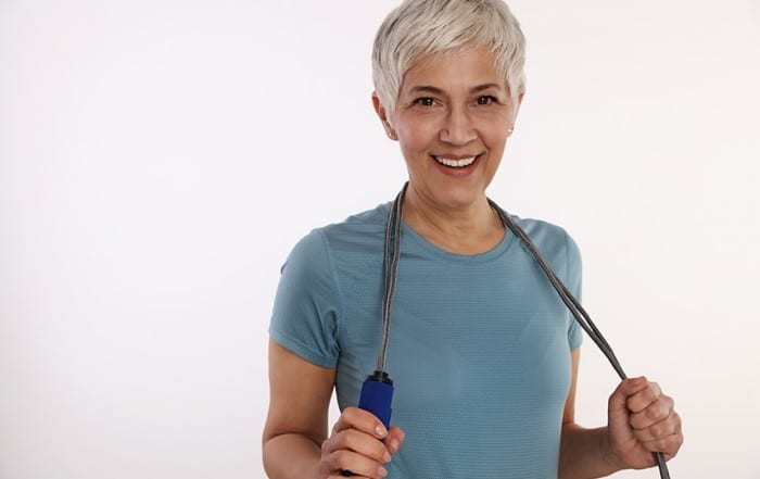 Smiling Mature Woman holding a jump rope. While she's great at skipping she knows the importance of not skipping dental exams with Dr. Mark Dunayer, Rockland County Dentist.