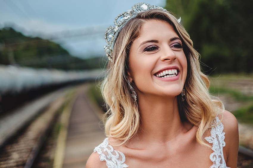 Blonde bride, showing off her crown and beautiful smile. She's showing off more than just the crown on her head.