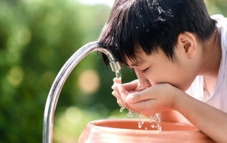 A young asisan boy drinks from a faucet, taking a drink. Fluoride benefits both children and adults by strengthening the enamel in our teeth.