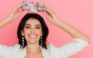 Woman smiling and putting a crown on her head